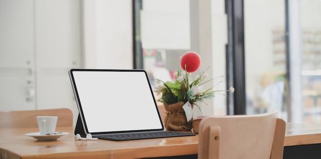 Tablet de tela em branco aberto no espaço de trabalho confortável com xícara de café e pote de árvore