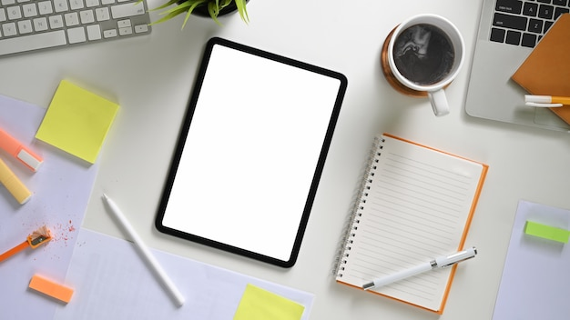 Tablet de tela em branco branco de espaço de trabalho e mesa de escritório criativa vista superior de vários equipamentos.