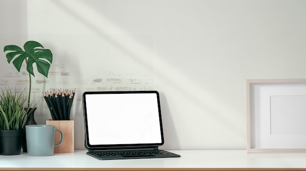 Tablet de tela em branco de maquete com teclado mágico e suprimentos na mesa de madeira.