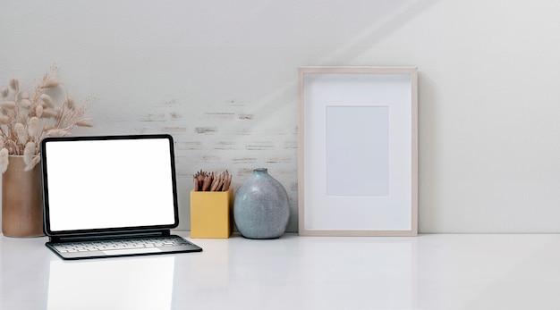 Tablet de tela em branco de maquete com teclado mágico na mesa superior branca.