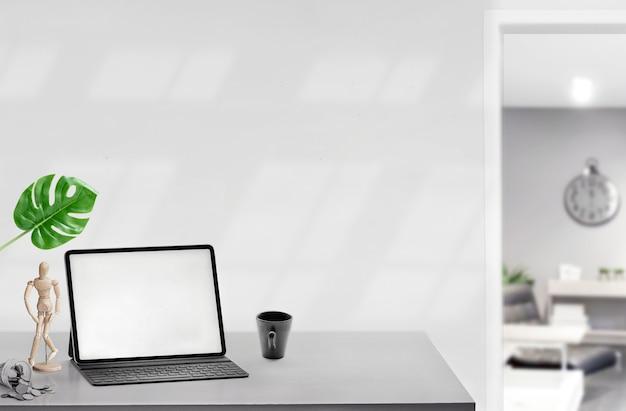 Tablet de tela em branco de maquete com teclado na mesa de madeira branca em casa moderna