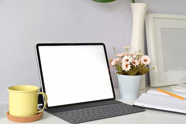 Tablet de tela em branco de maquete com teclado no espaço de trabalho de estúdio em casa