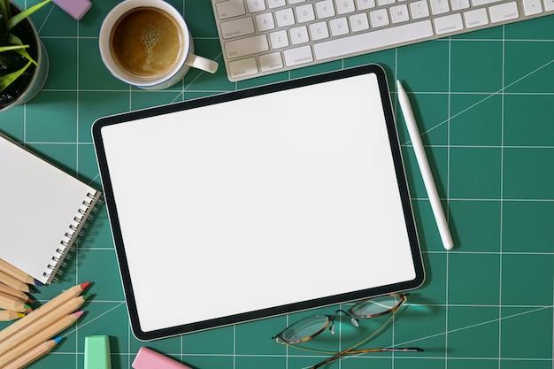 Tablet de tela em branco e designer gráfico fornece na esteira de corte verde
