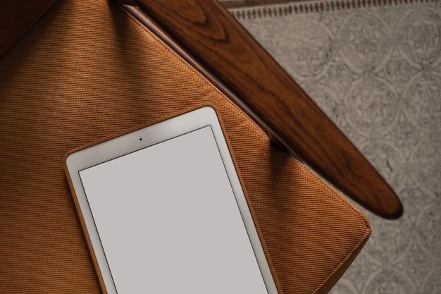 Tablet de tela em branco na cadeira vintage.