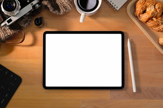 Tablet de tela em branco na mesa elegante de madeira com suprimentos de fotógrafo criativo
