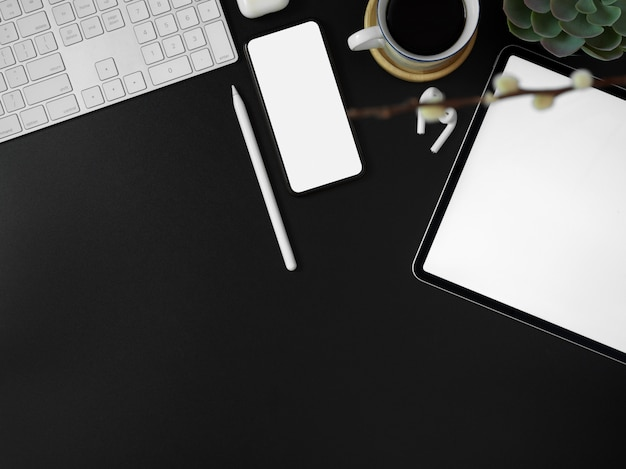 Tablet de tela em branco, smartphone, outros dispositivos digitais, decoração e espaço de cópia na mesa de escritório moderna escura