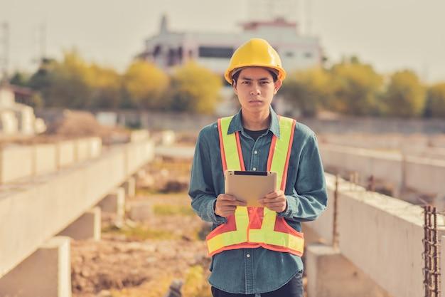 Tablet de uso do homem é fato de segurança foreman capacete amarelo segurança no canteiro de obras