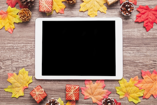 Tablet de vista superior, decorado com folhas de bordo coloridas na superfície de madeira