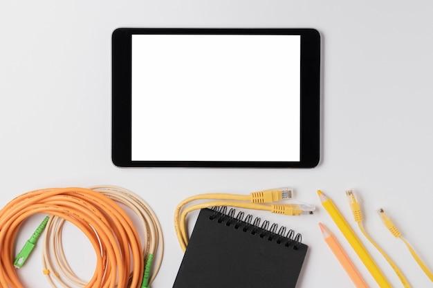 Tablet de vista superior perto de maquete de cabo ethernet