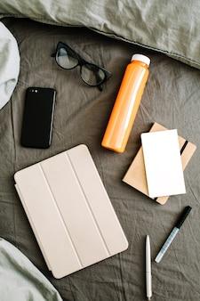 Tablet, diário, celular, suco natural, copos na cama com lençol cinza e travesseiros