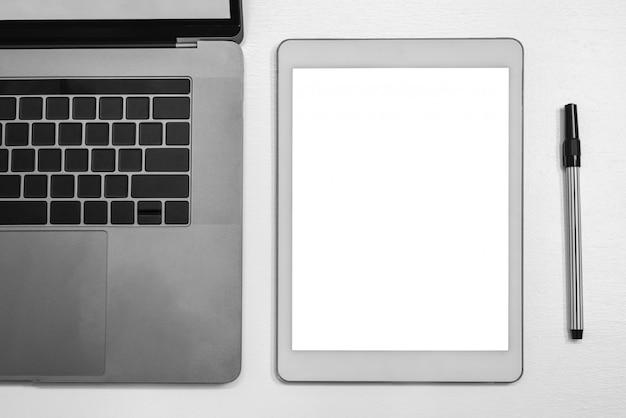 Tablet digital branco e caderno e caneta.