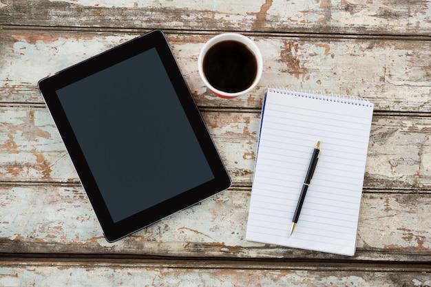 Tablet digital com bloco de notas e xícara de café