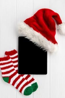 Tablet digital com chapéu de papai noel e meias em madeira branca. plano de natal