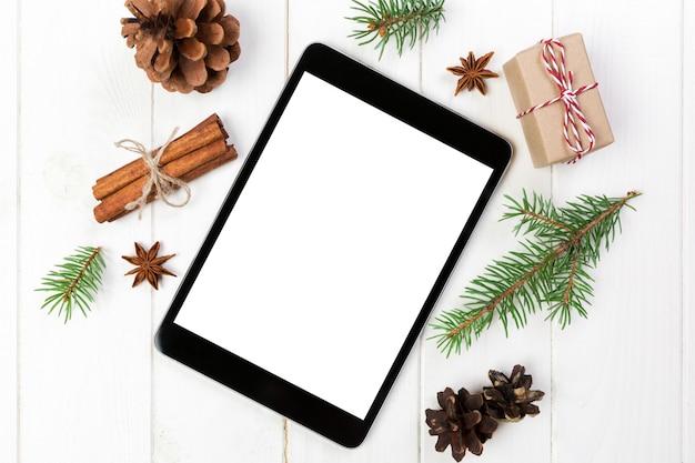 Tablet digital com decorações de fundo de madeira rústica de natal para apresentação do aplicativo. vista superior com copyspace