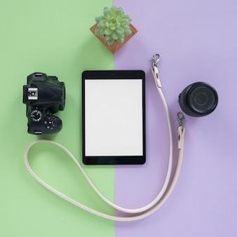 Tablet digital com tela em branco; câmera; lentes da câmera; cinto e planta suculenta sobre fundo duplo