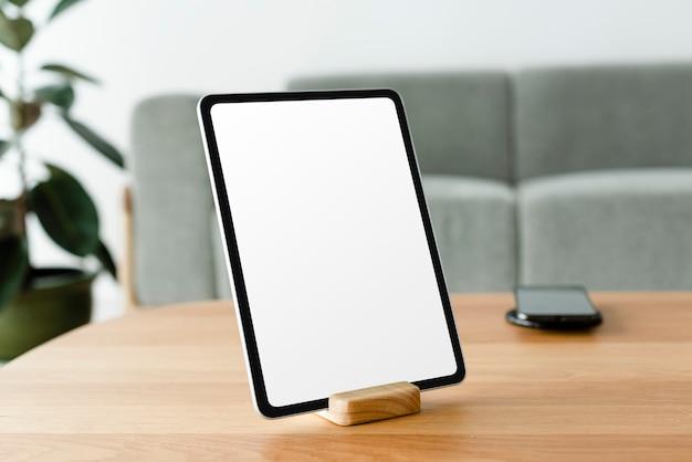Tablet digital com tela em branco na mesa de madeira
