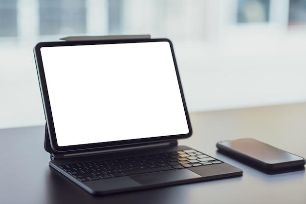 Tablet digital com tela em branco na mesa preta no escritório.