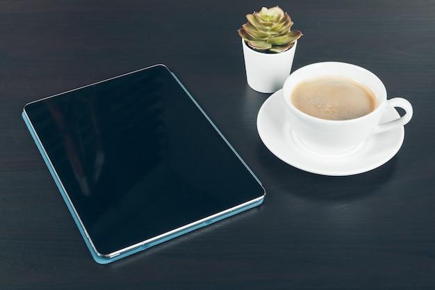 Tablet digital com tela preta, caneca de café e planta pequena em uma mesa de trabalho