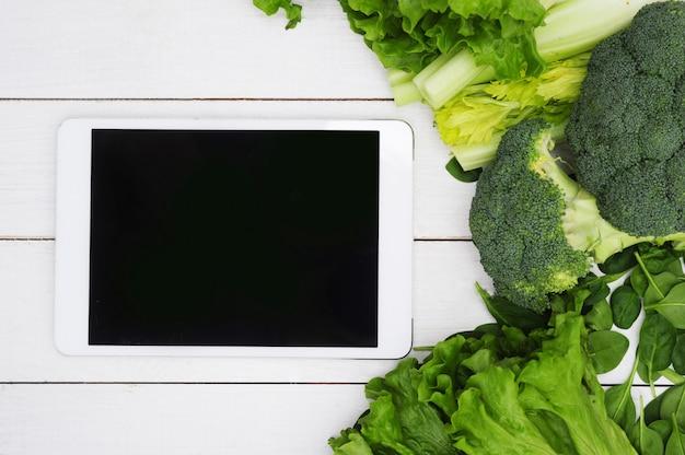 Tablet digital com tela preta e legumes, conceito de comida saudável