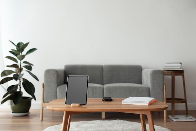 Tablet digital com tela preta em branco em uma mesa de madeira