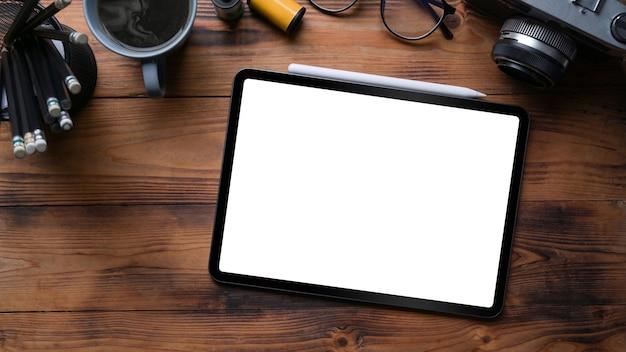 Tablet digital de vista superior, câmera e xícara de café em fundo de madeira.