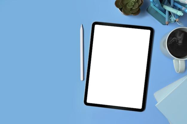 Tablet digital de vista superior, caneta stylus e suprimentos em fundo azul.