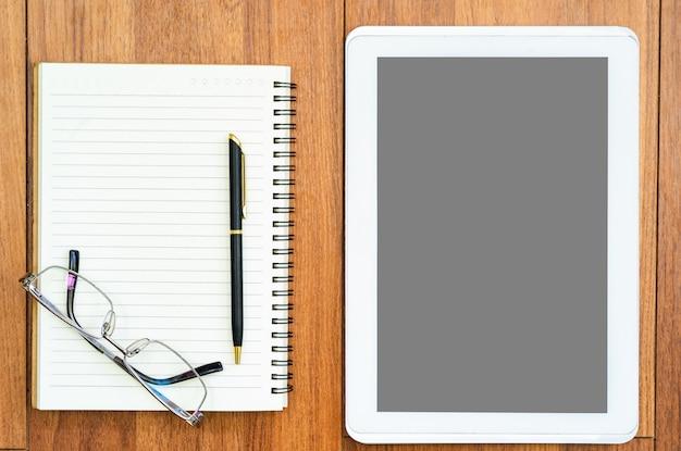 Tablet digital e bloco de notas no deck de madeira