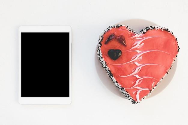 Tablet digital e bolo em forma de coração de dia dos namorados