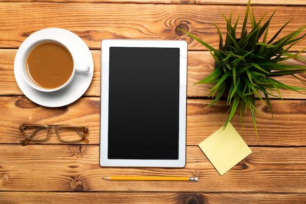 Tablet digital e xícara de café na mesa de madeira