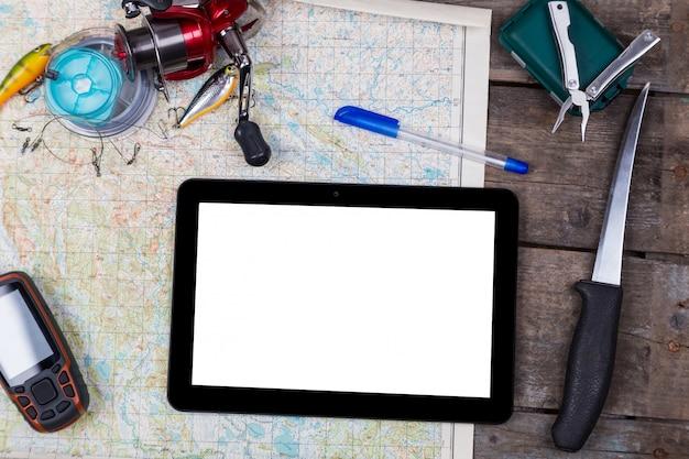 Tablet digital em branco com equipamentos de pesca e navegador no mapa