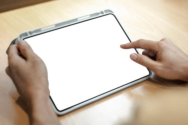 Tablet digital em branco em uma mesa de madeira clara