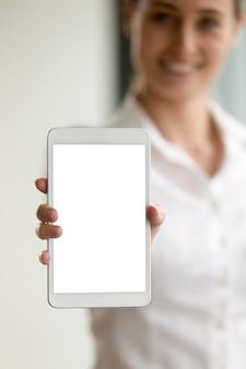 Tablet digital em branco na mão da mulher turva
