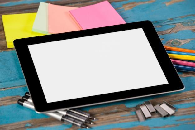 Tablet digital em canetas, alfinetes, lápis de cor e notas autoadesivas