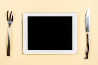 Tablet digital entre o garfo e butterknife no fundo bege