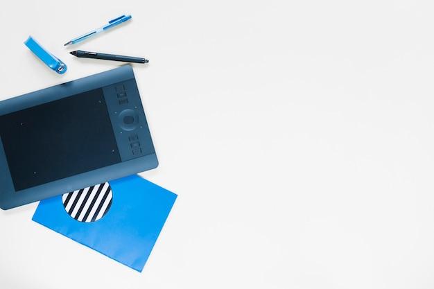 Tablet digital gráfico e artigos de papelaria no fundo branco