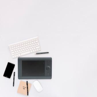 Tablet digital gráfico; teclado; mouse e celular com caneta em fundo branco