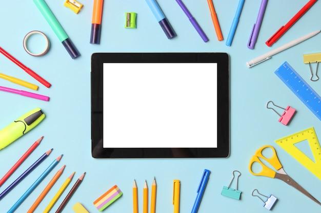 Tablet digital moderno e papelaria escolar em uma vista superior de fundo colorido