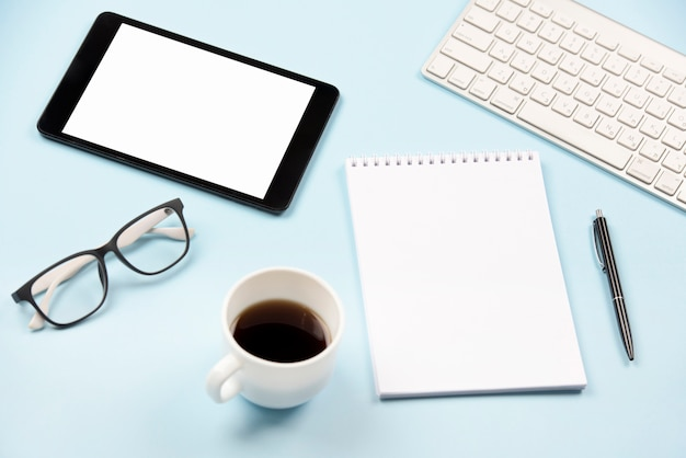 Tablet digital; óculos; xícara de café; bloco de notas espiral em branco; caneta e teclado em fundo azul