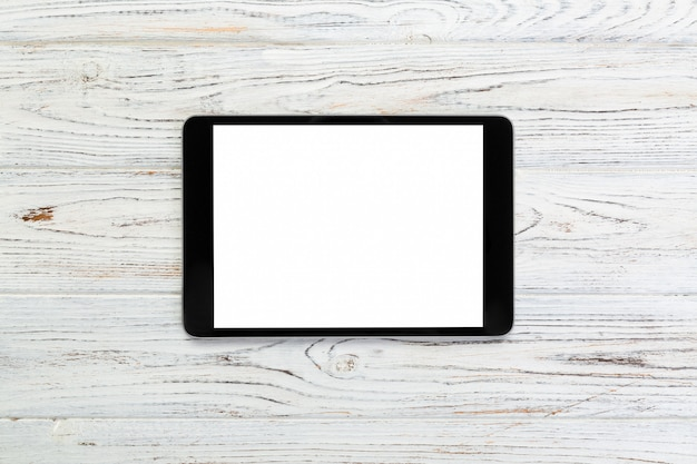 Tablet digital preto na mesa de madeira rústica, vista superior
