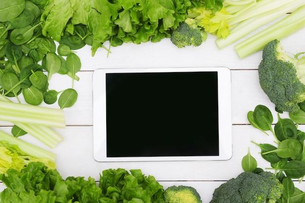 Tablet digital rodeado por legumes, conceito de comida saudável