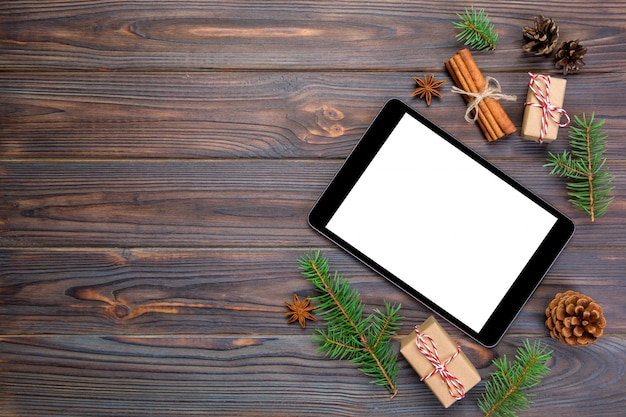 Tablet digital simulado acima com decorações de madeira rústicas de natal para apresentação do aplicativo. vista superior com copyspace