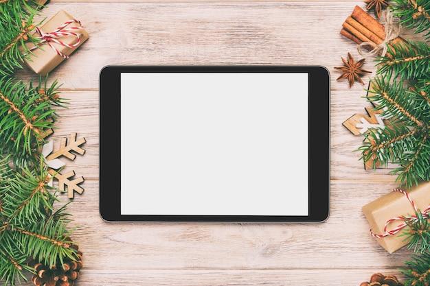 Tablet digital simulado acima com vintage rústico de natal, decorações de fundo de madeira tonificada para apresentação do aplicativo. vista superior com espaço de cópia