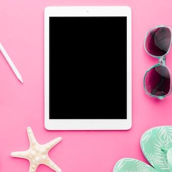 Tablet e acessórios de praia na superfície brilhante