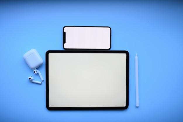 Tablet e com lápis e cápsulas de ar em fundo azul