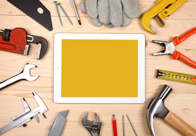 Tablet e conjunto de canalizações e ferramentas para obras de engenharia sanitária no fundo de madeira