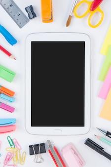Tablet e ferramentas de escola ou escritório no fundo branco e
