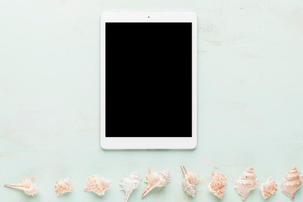 Tablet e linha de conchas no fundo claro