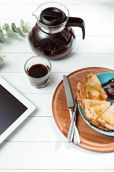 Tablet e panquecas com suco. café da manhã saudável