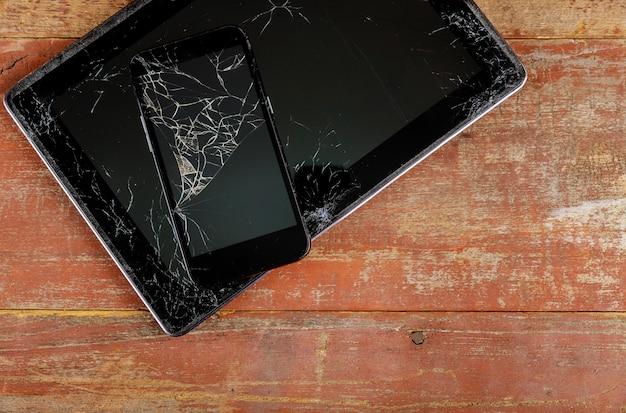 Tablet e telefone inteligente com tela de vidro quebrado no fundo madeira