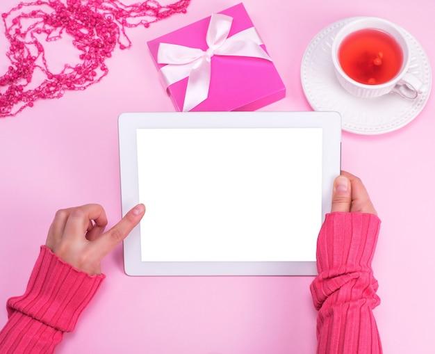 Tablet eletrônico com uma tela branca vazia nas mãos femininas